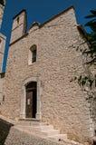 Beskåda gränden och kyrkan med stenkyrktorntornet i Helgon-Paul-de-Vence Royaltyfria Foton