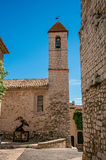 Beskåda gränden och kyrkan med stenkyrktorntornet i Helgon-Paul-de-Vence Royaltyfria Bilder