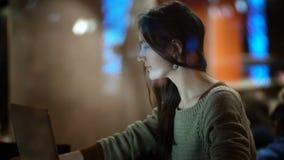 Beskåda inom fönstret på den härliga kvinnlign som använder smartphonen Kvinnasammanträde i kafé och arbete på bärbara datorn arkivfilmer