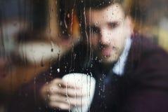 Beskåda mannen som ut ser fönstret fotografering för bildbyråer