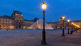 Beskåda på Louvrepyramiden och Pavillonen Rishelieu i aftonen, Paris, Frankrike Royaltyfria Bilder