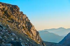 Beskåda på soluppgång i berg och vaggar på förgrund arkivfoto