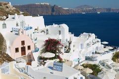 Beskåda till hotell byggnader med en havssikt till den vulkaniska calderaen i Oia, Grekland Royaltyfria Foton