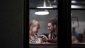 Beskåda till och med fönstret Romantiskt datum av unga härliga par Attraktivt man- och kvinnasammanträde i kafét lager videofilmer