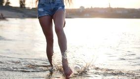 Beskåda underifrån av de kvinnliga benen, en kvinna promenerar kusten, den härliga kvinnlign som går på stranden bränning för hav lager videofilmer