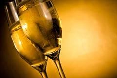Beskåda underifrån av två exponeringsglas av champagne med guld- bubblor Arkivbilder