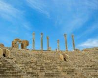 Beskåda upp trappan och visningställningarna till kolonner mot himmel på den forntida romerska teatern av Leptis Magna i Libyen arkivfoto