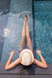 Beskåda uppifrån av en flicka som kopplar av i simbassängen Arkivfoton