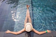 Beskåda uppifrån av en flicka som kopplar av i simbassängen Royaltyfri Bild