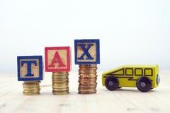 BESKATTA begreppet med träkvarter som staplas på av mynt med leksakbilen Arkivbilder