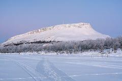 Beskåda av den Saana kullen från Kilpisjarvi laken i vinter, Finland Arkivfoton