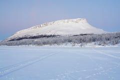 Beskåda av den Saana kullen från Kilpisjarvi laken i vinter, Finland Arkivbilder