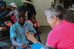 Beskickningsjuksköterska på kliniken med den unga haitira pojken Arkivbilder