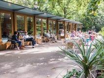 Beskyddare tycker om utomhus- tabeller på Caffe Russell i London Royaltyfria Foton