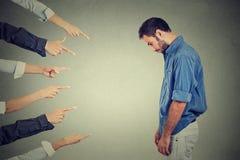 Beskyllning av den skyldiga personmannen man som ser ner fingrar som pekar på honom Arkivfoton