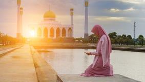 Beslöjad islamisk kvinna som bär ett burkaanseende i en stråle av över huvudet ljus i atmosfäriskt mörker royaltyfria foton