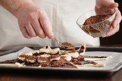 Beslag van de chef-kok omhoog sluit het gietende cake in een bakvorm, Royalty-vrije Stock Foto's