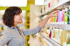 Beslut för kvinnadanandeshopping i apotek Arkivfoton