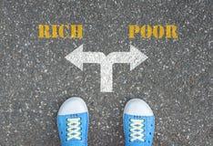 Beslut som ska göras på tvärgatan - rikt eller fattigt royaltyfri fotografi