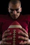Beslutsam amerikansk fotbollsspelare som rymmer en fotboll med båda hans händer Arkivbild