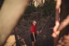 Beslutsam flicka som ser utomhus- utrustning under hinderkurs arkivbild