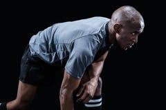 Beslutsam idrottsman som böjer, medan spela rugby Royaltyfri Foto