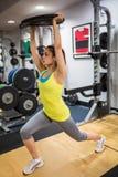 Beslutsam kvinna som gör utfall, medan rymma en vikt över huvudet Arkivbild