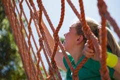 Beslutsam kvinna som klättrar ett netto under utbildning för hinderkurs royaltyfri bild