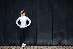 Beslutsam kvinna som vilar, når att ha joggat i staden Fotografering för Bildbyråer