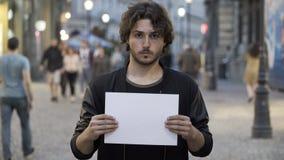 Beslutsam man som rymmer ett baner för tomt papper på gatan med kopieringsutrymme för text lager videofilmer