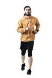 Beslutsam ung jogger i omslag med hörlurar som kör in mot kamera fotografering för bildbyråer