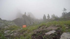 Beslutsam ung spring för konditionkvinnalöpare på härligt bergmaximum över molnhavet lager videofilmer