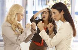 Beslutsamma affärskvinnor som slåss på arbetsplatsen Fotografering för Bildbyråer