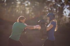 Beslutsamma kvinnor som öva att boxas under hinderkurs royaltyfria foton