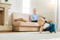 Beslutsamt emotionellt behandla som ett barn krypning medan hans fader som ser honom Arkivbild