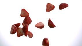 Besnoeiing in twee stukken aardbeien die in lucht neer in langzaam motietafelblad vliegen stock footage