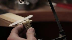 Besnoeiing van een zilveren baar met een figuurzaag stock footage