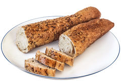 Besnoeiing van het Baguette de Integrale Brood in Plakken op Witte Geïsoleerde Plaat - Royalty-vrije Stock Afbeelding