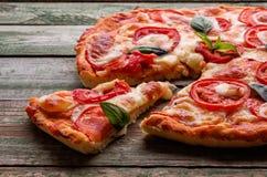 Besnoeiing van plakpizza met kaas op groene houten lijst Royalty-vrije Stock Foto