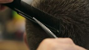 Besnoeiingen van de close-up bemant de mannelijke kapper haar met schaar in een kapperswinkel stock videobeelden