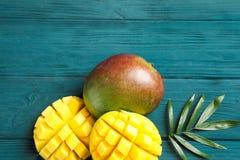 Besnoeiings rijp mango's en palmblad op houten achtergrond royalty-vrije stock afbeeldingen