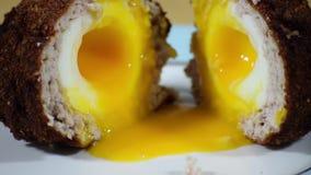 Besnoeiings Schots ei met dooier die uit afscheiden stock video