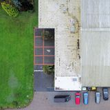 Besnoeiings verticale mening van een oude lelijke tenniszaal met geparkeerde binnen auto's Royalty-vrije Stock Foto