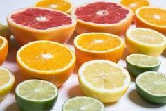 Besnoeiingscitrusvruchten van verschillende kleuren op wit Gesneden citroen, sinaasappel, kalk en grapefruit Royalty-vrije Stock Fotografie