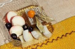 Besnoeiingsfruit in honing wordt geplaatst die Stock Fotografie