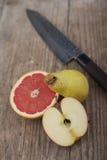 Besnoeiingsfruit op houten oppervlakte met mes Royalty-vrije Stock Afbeeldingen