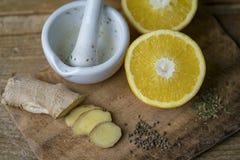Besnoeiingsgember, sinaasappel en kruiden met mortier en stamper stock fotografie