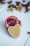 Besnoeiingsgranaatappel en wortel in de vorm van hart op een witte lijst Stock Foto