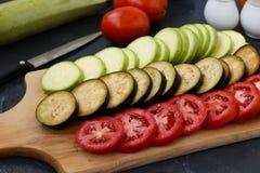 Besnoeiingsgroenten: de courgette, de aubergines en de tomaten worden gevestigd op een houten raad op een donkere achtergrond royalty-vrije stock afbeeldingen