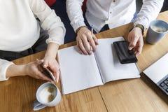 Besnoeiingsmening die van vrouw en man handen telefoons houden De kerel houdt pen op dagboek in hand Zij dragen kostuums Ook is e royalty-vrije stock afbeeldingen
